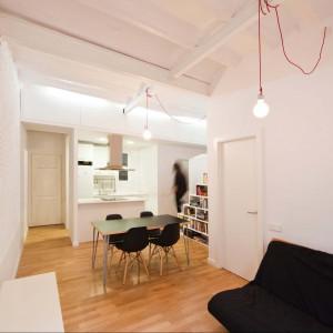 Małe mieszkanie jest otwarte, elementem, który je spaja jest piękna biała cegła na ścianach. Fot. Eva Cotman.