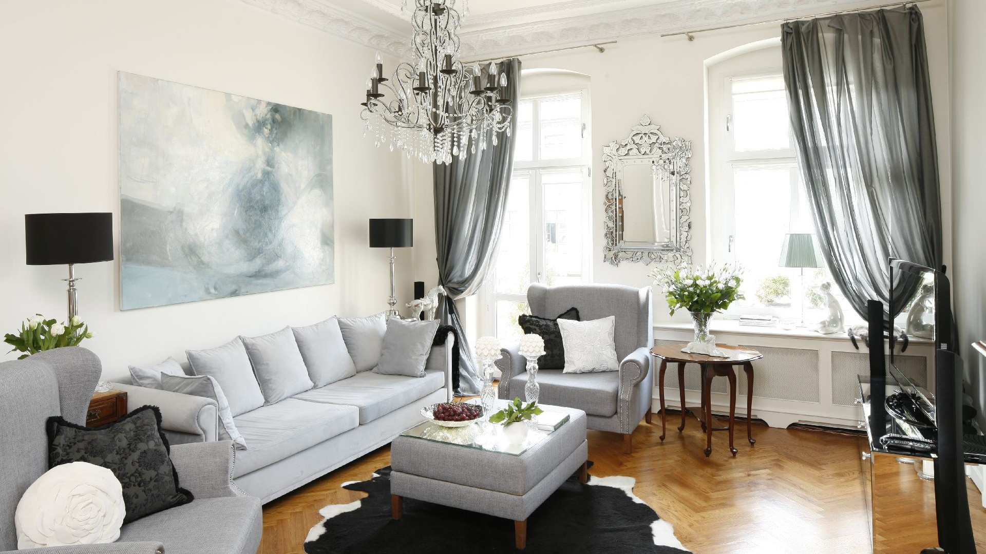 Pokój dzienny w pięknym klasycznym stylu. Funkcję stolika kawowego pełni wsalonie duża pufa. Wtej dość nietypowej roli sprawdza się znakomicie. Fot. Bartosz Jarosz.
