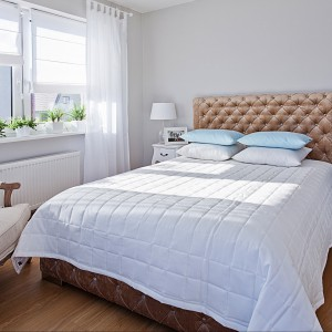 Sypialnia Romantica to jasne, lekkie tkaniny. Biel doskonale łączy się z delikatnym błękitem poduszek. Fot.Dekoria.