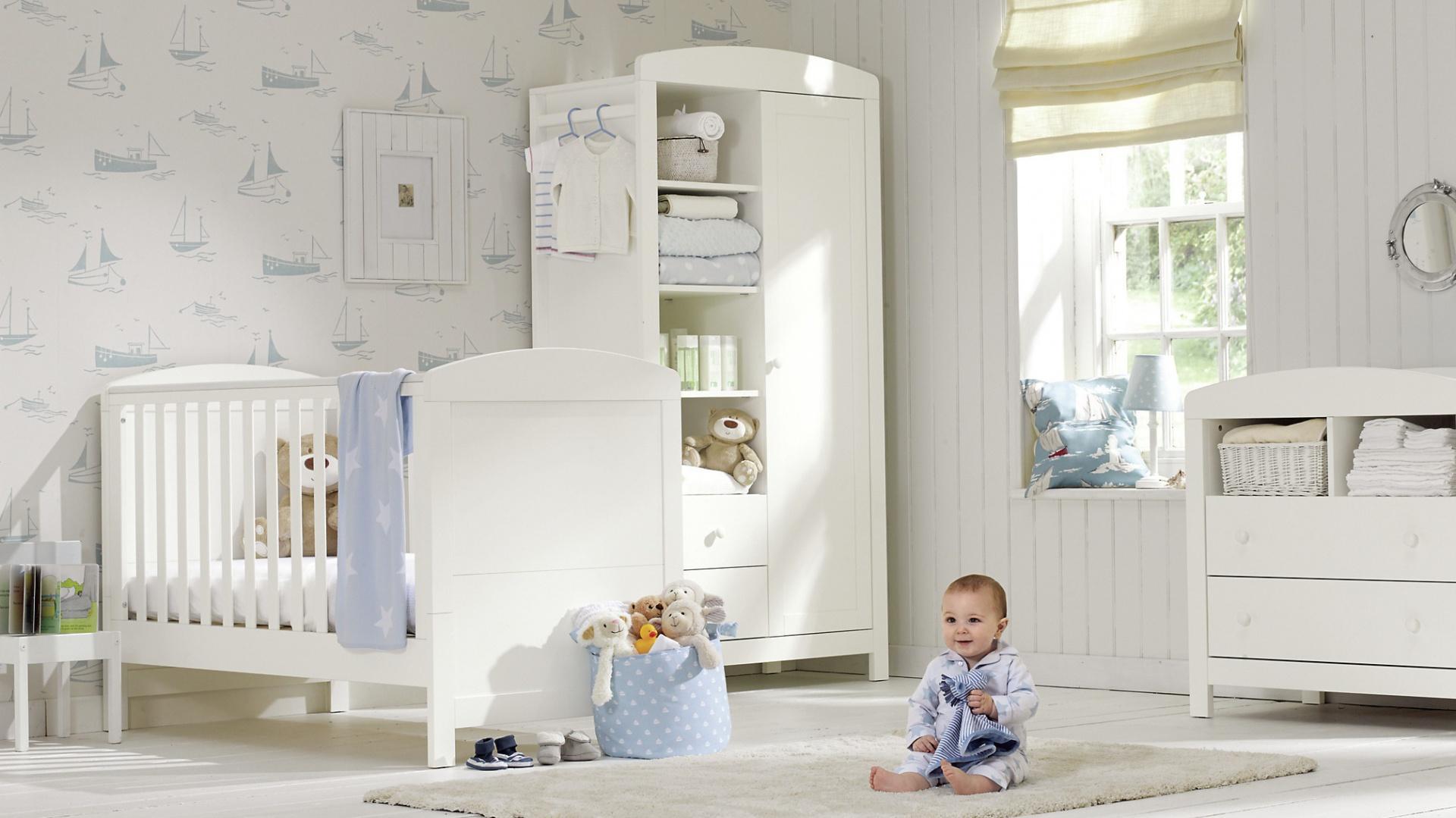 Błękitne akcenty na tapecie, a także niebieska pościel i akcesoria subtelnie ożywiają białe wnętrze. Fot. Mothercare.