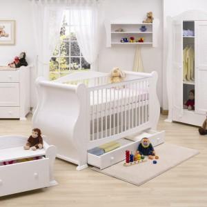 Białe wnętrze ociepla podłoga w kolorze drewna oraz liczne zabawki. Fot. JK Interior.