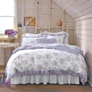 Pastelowe fiolety w połączeniu z bielą oraz kwiatowymi motywami tworzą wyjątkową sypialnię. Fot. Modern Magazin.