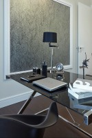 Stylowy gabinet w rezydencji Foksal. Uwagę zwraca nietypowy regał z ukośnymi półkami, tworzącymi romby.  Delikatna szarość dodaje elegancji, a biurko jest nowoczesnym akcentem.