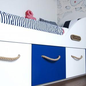Łóżko w pokoju nie tylko służy do spania. Dzięki czterem szufladom pełni też rolę praktycznej skrytki. Fot. Benjamin Moore.