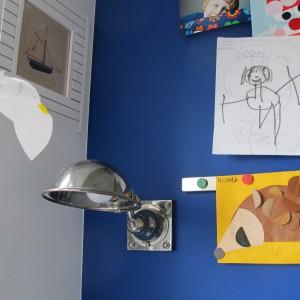 Ścianę przy wnękowej szafie zdobi farba Aura w odcieniu granatu Patriot Blue, na tle której bardzo ładnie prezentują się kolorowe rysunki dziecka. Fot. Benjamin Moore.