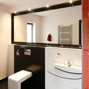 Lustro w stylowej ramie a la Ludwik XV zawieszone na całą długość gościnnej łazienki nadało nowoczesnej aranżacji szczyptę glamour. Projekt Wielicki & Hoffman. Fot. Bartosz Jarosz.
