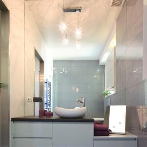Duża tafla lustra zamontowana została na całej ścianie tuż za strefą umywalkową. Wraz z jasnymi kafelkami i białym wyposażeniem optycznie podwaja ona przestrzeń łazienki.  Projekt Ministerstwo Spraw we Wnętrzach. Fot. Bartosz Jarosz.