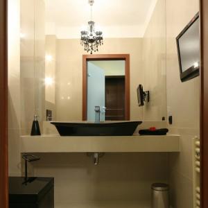 W utrzymanej w ciepłej, jasnej tonacji łazience duża tafla lustra dodatkowo ją rozjaśnia, tak że czarna ceramika, jak i dodatki nie zakłócają przytulnej atmosfery.  Projekt Piotr Stanisz. Fot. Bartosz Jarosz.