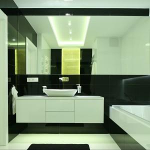 W czarno-białej łazience duże tafle luster podkreślają czystość aranżacji przestrzeni. Projekt Agnieszka Hajdas-Obajtek. Fot. Bartosz Jarosz.