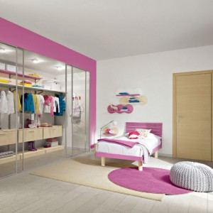 Różowa powierzchnia przy garderobie, łóżko i dywan w tym samym kolorze nadają wyrazisty charakter białemu wnętrzu. Fot. Colombini Casa.