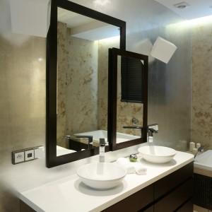 Na ogromnej, matowej tafli lustra zamontowanej na jednej ze ścian łazienki dwie nachodzące na siebie ramy wydzielają jego powierzchnie użytkowe. Projekt Katarzyna Koszałka. Fot. Bartosz Jarosz.