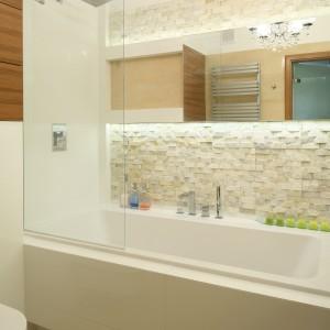 W jasnej, stonowanej łazience zamontowana tuż nad wanną długa tafla lustra stanowi ciekawy element dekoracyjny. Projekt Małgorzata Mazur. Fot. Bartosz Jarosz.