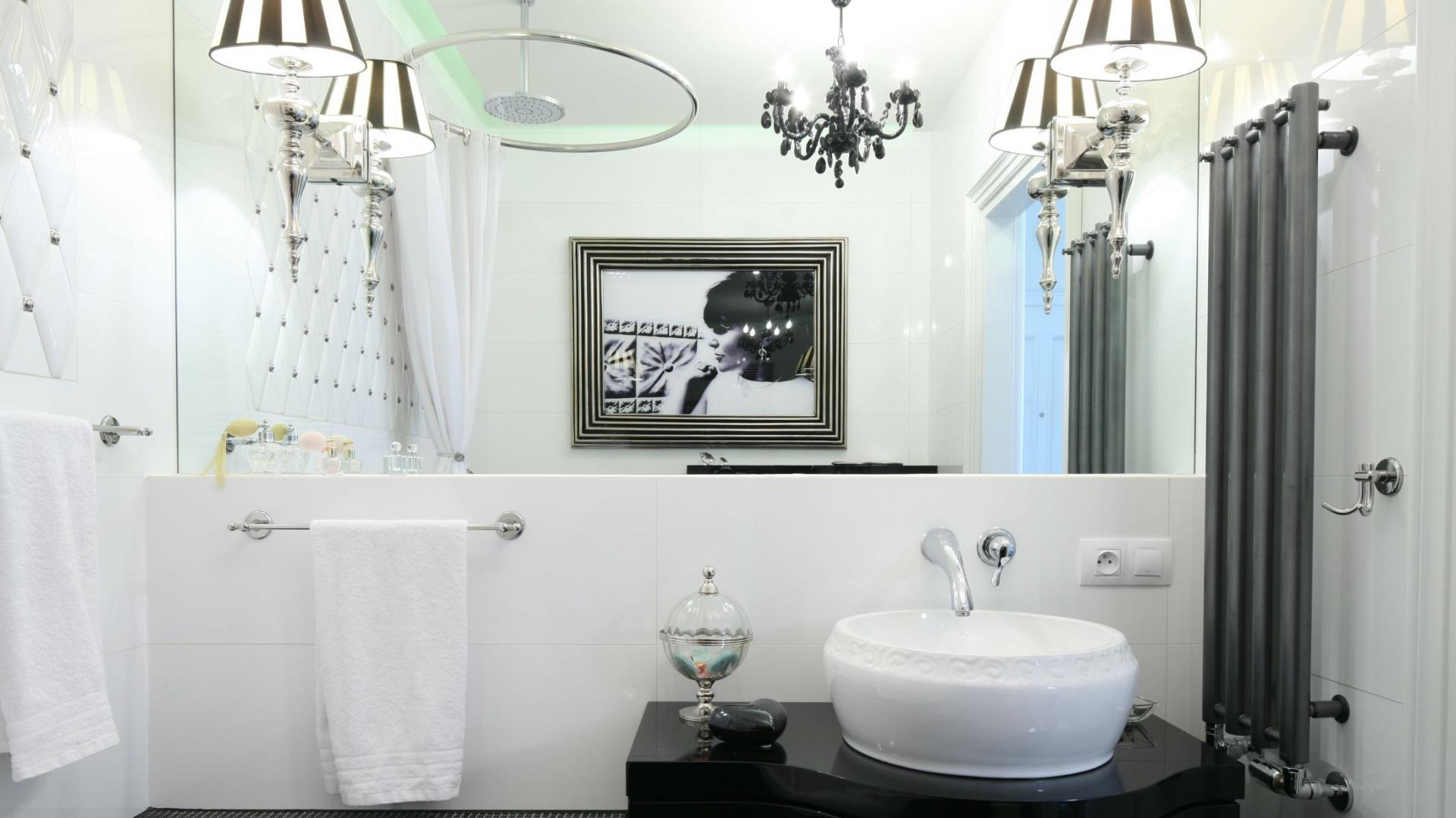 Czarno-białe wnętrze glamour, dzięki ogromnej tafli lustra ulokowanej na jednej ze ścian, zachwyca podwójnie. Projekt Małgorzata Galewska. Fot. Bartosz Jarosz.