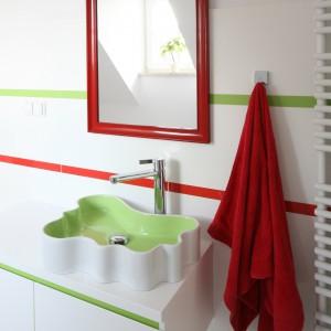 Czerwona rama prostego, niedużego lustra ożywia białą łazienką doskonale korespondując z innymi, kolorowymi elementami wystroju wnętrza. Projekt Katarzyna Merta-Korzniakow. Fot. Bartosz Jarosz.