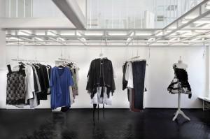 Życzeniem naszej klientki Joanny Klimas było stworzenie miejsca, które łączy w sobie sklep, kawiarnię i wzorcownię. Miejsca, w którym klientki nie tylko mogłyby przymierzyć projektowane przez nią kreacje, ale także podyskutować przy dobrej kawie i zrelaksować się przeglądając albumy mody z prywatnych zbiorów projektantki. Ponadto projektantce zależało na uzyskaniu przestrzeni, która umożliwi organizowanie autorskich pokazów mody. Punktem wyjścia projektantów atelier na Muranowskiej było pytanie: jak połączyć styl projektowanych przez Joannę Klimas ubrań ze stylem wnętrza tak, aby stanowiły organiczną całość? Stworzyliśmy wyraziste i minimalistyczne wnętrze, które jest tłem dla projektów Joanny Klimas. Udało się uzyskać otwartą przestrzeń składającą się z dwóch wysokich sal (4,5 metra) wykończonych oryginalną socrealistyczną sztukaterią i połączonych monumentalnym portalem. Stworzenie antresoli pozwoliło na uzyskanie dodatkowej powierzchni, w której na co dzień znajdują się stoliki kawiarni i czytelni, a podczas pokazów mody zmienia się w rodzaj trybuny z której oglądane są pokazy. Lekka i ażurowa konstrukcja antresoli pokrytej szkłem nie przytłacza wnętrza, a światło dzienne wpada swobodnie na niższy poziom gdzie znajduje się wielofunkcyjna szafa. Eleganckie schody, których konstrukcja nawiązuje kształtem do krawieckich nożyc zachowują lekkość mimo przenoszenia ogromnych obciążeń. Cała antresola została podświetlona ponad 120 świetlówkami o możliwości regulacji światła w 6 strefach ekspozycyjnych. Pozwala to na doskonałe oświetlenie przestrzeni pokazowej na dolnym poziomie lokalu. Uzyskane wnętrze odpowiada założeniom naszej klientki. Otwarta przestrzeń, w której ubrania powstają wprost na oczach klientek, niczego nie ukrywa.