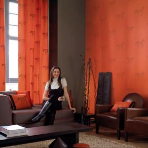 Pomarańczowa tapeta Saint Germain oraz zasłony Rive Gauche marki Casadeco stanowią piękne tło dla eleganckich skórzanych mebli. Fot. Casadeco.