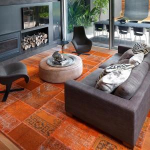 Pomarańczowy dywan ożywił ciemnoszarą aranżację. Fot. RC+D.