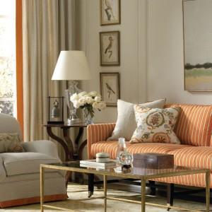 Stonowany pomarańcz na sofie, zasłonach i poduszkach dekoracyjnych znakomicie prezentuje się w klasycznym wnętrzu. Fot. Lee Jofa.
