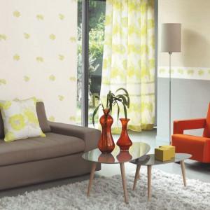 Pomarańczowy fotel i szklane dekoracje wnoszą pozytywną dawkę energii do zielono-szarego salonu. Fot. Casadeco.