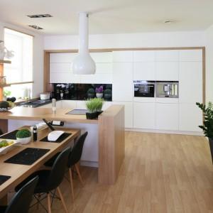Przestrzeń kuchni wyznacza z jednej strony wysoka zabudowa na całej szerokości ściany, z drugiej – półwysep, pełniący m.in. rolę strefy gotowania. Projekt: Małgorzata Błaszczak. Fot. Bartosz Jarosz.