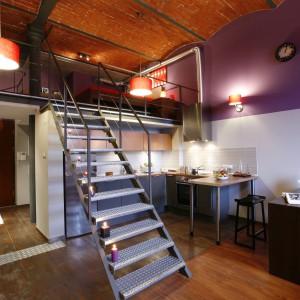Ten apartament utrzymany w industrialnym stylu znajduje się w dawnej łódzkiej przędzalni. Miejsce na kuchnię wyznaczono tuż pod schodami. Zastosowane materiały oraz kolorystyka doskonale wpisują się w klimat tego miejsca. Projekt: Luiza Jodłowska. Fot. Marcin Onufryjuk.