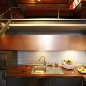 Kolor i rodzaj wykończenia frontów nawiązują do oryginalnych materiałów wykorzystanych w architekturze loftu (czerwonej cegły, stalowych elementów). Na górnych mamy dekor szczotkowanej miedzi, na dolnych – kolor stali. Projekt: Luiza Jodłowska. Fot. Marcin Onufryjuk.