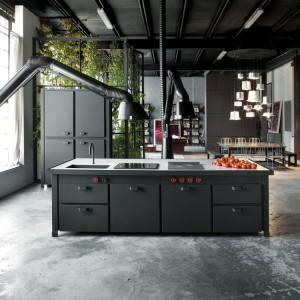 Ten loft znajduje się w Mediolanie. Duża wyspa w otwartej strefie dziennej wyznacza przestrzeń kuchni. Stanowi centrum gotowania, przechowywania i przygotowania posiłków. Szczególną uwagę zwraca okap – wygląda bowiem jak duża, stojąca lampa. Projekt: Minacciolo SPA. Fot.  Minacciolo SPA