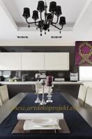 Efektowna kuchnia w stylistyce glamour. Wnętrze utrzymane jest w klasycznych, stonowanych barwach, meble kuchenne natomiast mają  prostą i oszczędną formę. Ozdobności dodaje duży żyrandol oraz rolety z fioletowo-złotym, przykuwającym uwagę dekorem.
