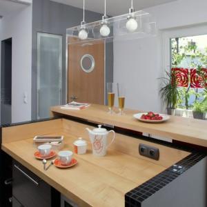 Wyspa została oświetlona dekoracyjną lampą wiszącą o prostym, nowoczesnym kształcie. Idealnie wpisuje się ona w stylistykę wnętrza kuchni. Projekt: Anna Gruner. Fot. Monika Filipiuk-Obałek.
