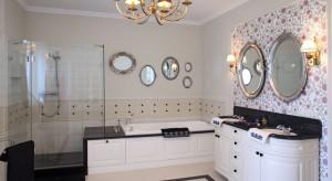 Zaaranżowany w stylu angielskim, wytworny salonik kąpielowy kusi perspektywą odprężającej kąpieli w pianie. Piękne kwiaty na ścianie nad umywalką, zdają się przyciągać swoim wonnym zapachem.