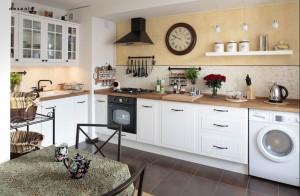 Ta kuchnia mieści w sobie dużo stylowych detali, które nadają jej ciepły i domowy charakter. Jest przy tym prosta, ale funkcjonalna - biała zabudowa pomieści wszystko, co niezbędne. Na gości i domowników czeka również mały stół.