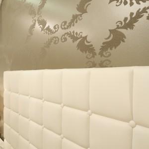 Połyskująca tapeta stanowi doskonale tło,które podkreśla białe,  tapicerowane łóżko z wysokim zagłówkiem. Proj.Karolina Łuczyńska. Fot.Bartosz Jarosz.