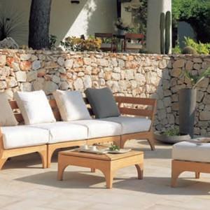 Sofa z kolekcji Village marki Ethimo z teakową ramą i miękkimi poduchami. Fot. Ethimo.
