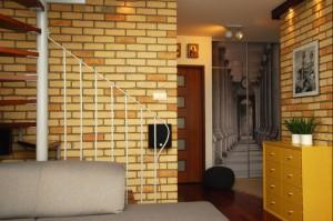 Salon w naturalnych kolorach - szarościach skomponowanych z beżami i żółcią. Proste wnętrze, bez zbędnych detali, zwraca uwagę kolorystyką i fakturami.  Jasna ściana z cegły, ściana z  ozdobnym tynkiem - połączone w jednej przestrzeni dają ciekawy efekt. Intryguje również fototapeta w holu - bardzo dobrze dobrana, dająca złudzenie przedłużenia pokoju.