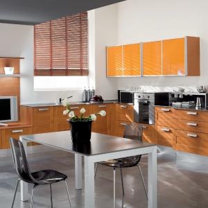 Kolor pomarańczowy w spokojnym odcieniu zastosowano tylko na szafkach górnych, dzięki czemu  ładnie wtapia się w aranżację kuchni. Nie dominuje, ale nadaje jej oryginalny charakter. Fot. Mario Cucine.