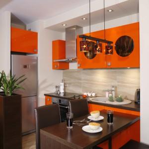 Najmocniejszy akcent stanową fronty szafek w kolorze pomarańczowym, których błyszcząca, lakierowana powierzchnia pomaga wizualnie powiększyć wnętrze. Soczysty, pełen energii kolor powtarza się na fragmentach ściany i sufitu w salonie. Projekt: Jolanta Kwilman. Fot. Monika Filipiku-Obałek.