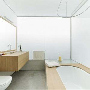 Zestaw biel i drewno to niewątpliwie udane połączenie łazienkowe. Klasa i odpoczynek w jednym. Fot. Inaki Leite, Dezanove House.