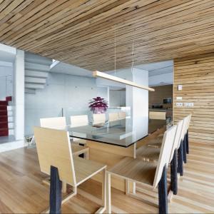 Minimalizm to cecha charakterystyczna tego domu. Tutaj również drewno w postaci krzeseł i lampy oświetleniowej. Fot. Inaki Leite, Dezanove House.