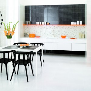 W kuchni dominuje biel, która nadaje jej lekkości. Wystarczyło zaledwie kilka dodatków w intensywnym pomarańczowym kolorze, aby wnętrze nabrało charakteru. Fot. Grupa Paradyż.