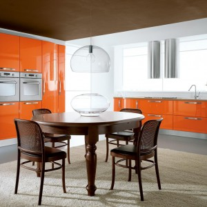 Fronty mebli są mocnym elementem kuchni. Lśniące, pomarańczowe powierzchnie doskonale uspokaja kolorystka i proste formy wszystkich pozostałych elementów wnętrza. Fot. Lube Cucine.