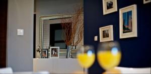 Nowoczesna przestrzeń, dopełniona intrygującymi detalami. Fototapeta nadaje wnętrzu wielkomiejski charakter. Czerń i szarość ścian idealnie komponuje się z białymi meblami.