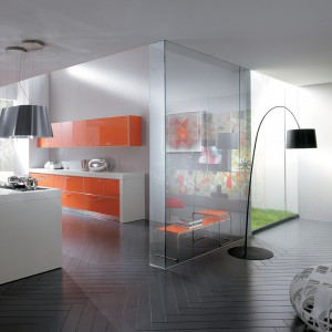Pomarańczowe fronty mebli w połysku uspokajają różne odcienie szarości zastosowane we wnętrze. Nadają one również nowoczesnej aranżacji ciepły charakter. Fot. Scavolini.
