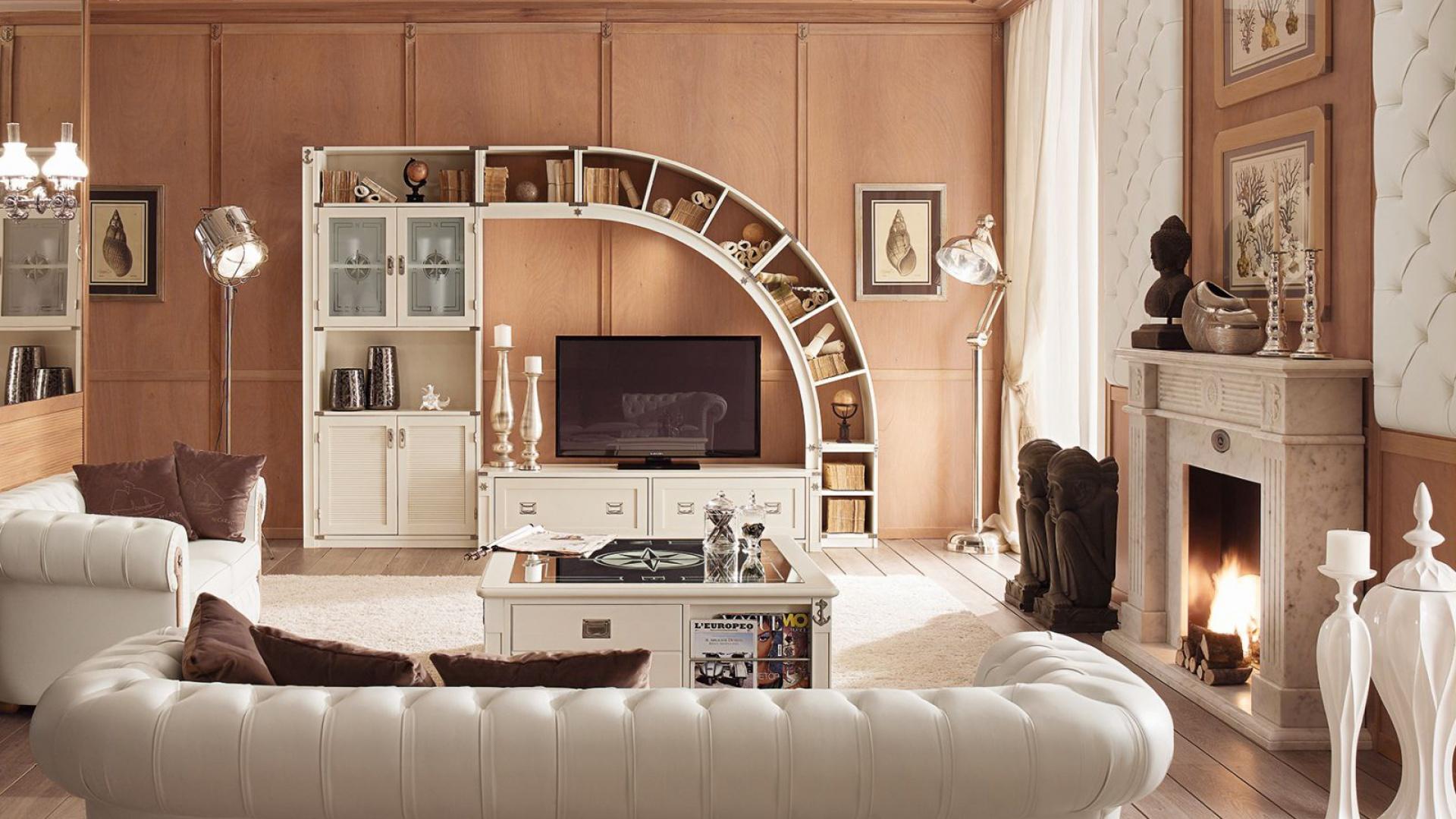 Oryginalna meblościanka i jasne wypoczynki wyróżniają się na tle ścian w kolorze drewna, tworząc ciepłą, elegancką aranżację. Fot. Caroti.