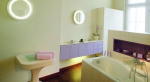 Przez każdą kostkę fioletowej mozaiki ze szkła przewija się złota nić. Uwodzicielsko mieni się w świetle lamp-luster, zapraszając do spędzenia czasu w łazience – ot, choćby przy kawie.