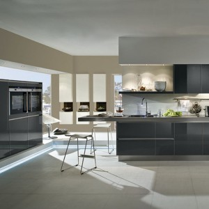 Bezuchwytowa kuchnia Stratos GL marki Häcker, której fronty o wysokim połysku w kolorze węgla z metalicznym efektem kontrastują ze świeżością bieli. Mocny akcent stanowią wysokie i smukłe szafki wiszące. Fot.  Häcker.
