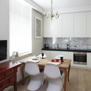 Kącik jadalniany tworzą: oczyszczony ze starych lakierów stół i cztery białe, lekkie klasyki designu - krzesła proj. Vernera Pantona. Fot. Bartosz Jarosz.