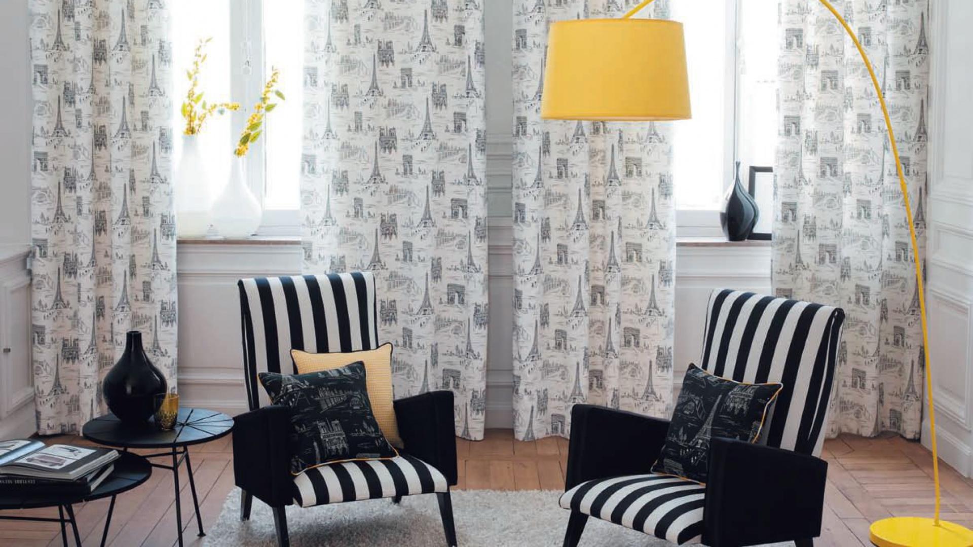 Żółta lampa podłogowa wnosi do biało-czarnego wnętrza odrobinę młodzieńczej ekstrawagancji. Zasłony z kolekcji Paris marki Casadeco. Fot. Casadeco.