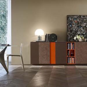Szafka z pomarańczowymi detalami delikatnie ożywi salon w brązach. Fot. Mobilgam.it.