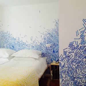 Białe ściany są tłem dla dynamicznej kompozycji składajacych się z drobnych,niebieskich elementów. Proj.Pikxtil Studio. Fot.Au Vieux Panier.
