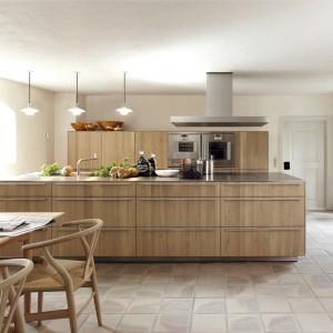 Meble z kolekcji b3 firmy Bulthaup. Centralnym punktem kuchni jest funkcjonalna wyspa, która oddziela część roboczą od znajdującej się w pobliżu jadalni. Stół i krzesła idealnie pasują do frontów mebli.
